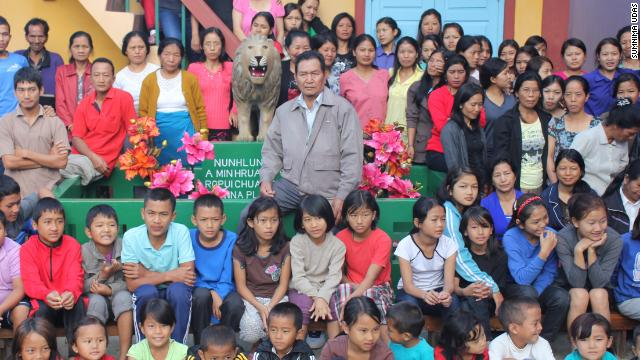 Ziona, center, with his has 39 wives, 86 children and 35 grandchildren in rural Baktwang village, India.