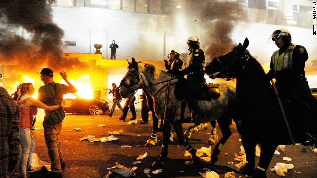 Police on horseback try to move an unruly crowd in June in Vancouver, British Columbia, Canada.