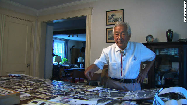 Susumu Ito displays the large number of photos he took in Europe during his US Army service in WWII