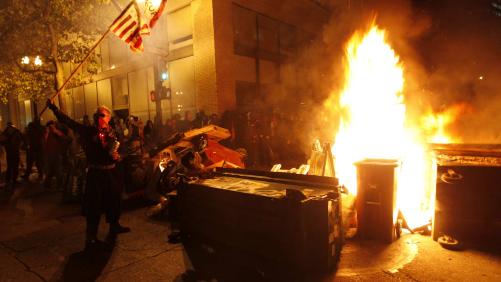 Occupy Oakland protesters set fire to trash to make a barricade against police early Thursday. Police said they surrounded and arrested dozens of protesters wielding shields.