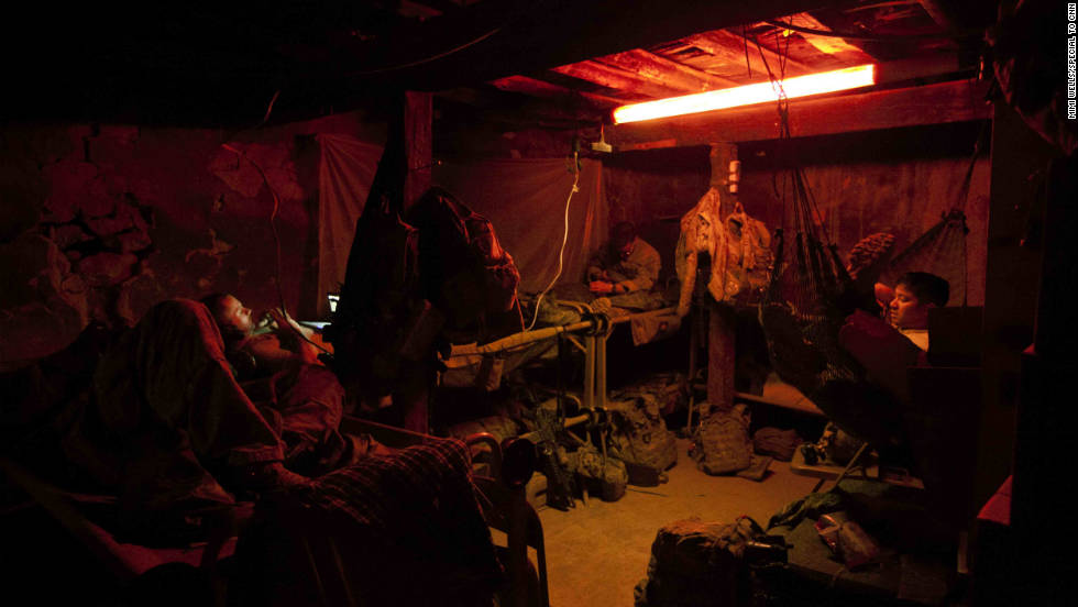 Conditions at Checkpoint 2.5 are bare, but the platoon makes the most of it. Sgt. Patrick Trout, who is on his second deployment, swings from a hammock he brought from the base. Others watch movies and listen to music. The men sleep in shifts, and when they are not in one of the two covered rooms in the outpost, they are required to wear full body armor.