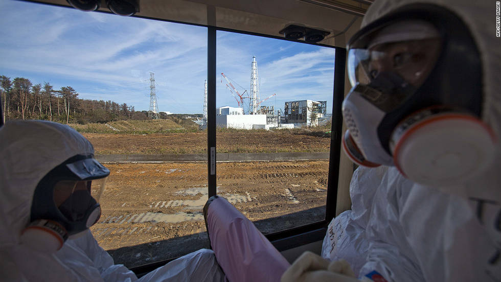 People wearing protective suits and masks ride on a bus past the crippled Fukushima Daiichi nuclear power station in Okuma, Japan, on Saturday, November 12 2012.  Journalists got their first ground-level glance  around the stricken facility, eying shells of reactor buildings, tons of contaminated water, and workers still scurrying to mitigate damage from a crisis that began eight months ago.