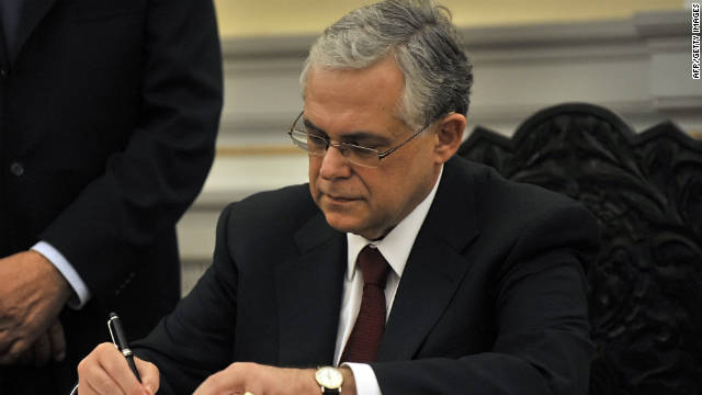 Lucas Papademos signs documents after being sworn in as Greece's new Prime Minister in Athens on Friday.