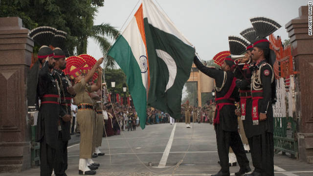 Pakistani and Indian soldiers lower the flags of their countries during a daily ceremony at the Wagha border near Lahore on July 17, 2011.