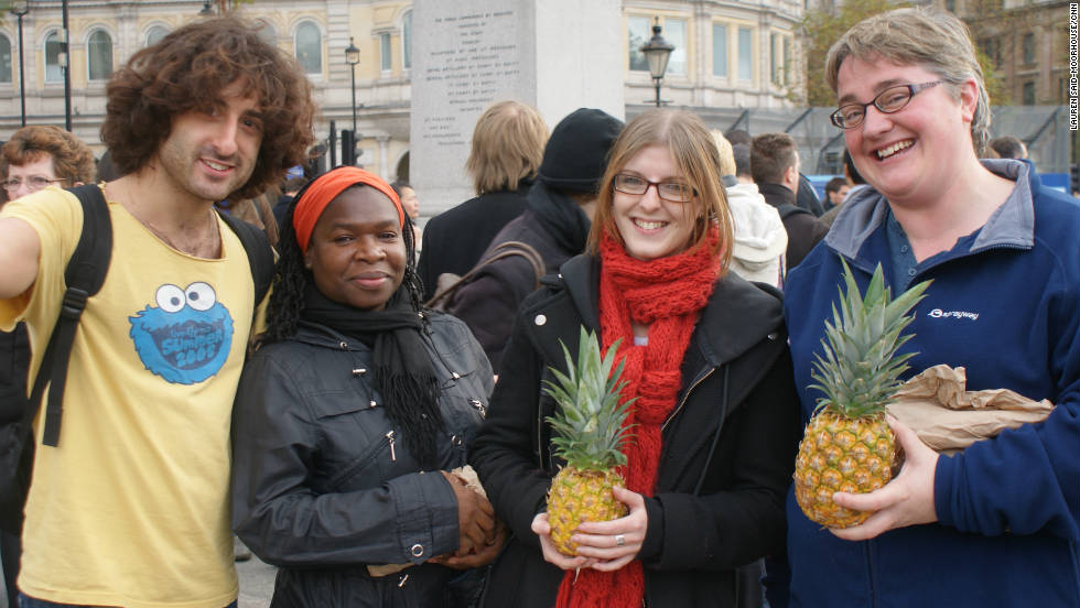 "Volunteers from a Jewish charity show off waste pineapples which are being given to the public. Shelley Shocolinksky-Dwyer (far right) says: ""We wanted to help raise awareness and spread the message about food waste in the United Kingdom."""