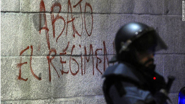 "Graffiti says ""Down with the regime"" on Spain's parliament building near a riot officer during a protest before elections this month."