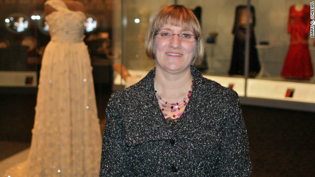 Exhibition Curator Lisa Kathleen Graddy in front of Michelle Obama's dress, which is a centerpiece of the exhibit.