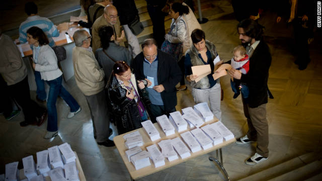 Voters take their ballot papers before casting them for Spain's general election Sunday in Barcelona.