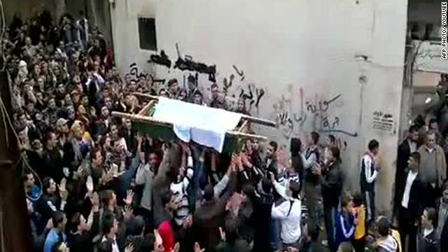 Syrian mourners carrying the coffin of a victim killed in recent violence in Tal Kalakh