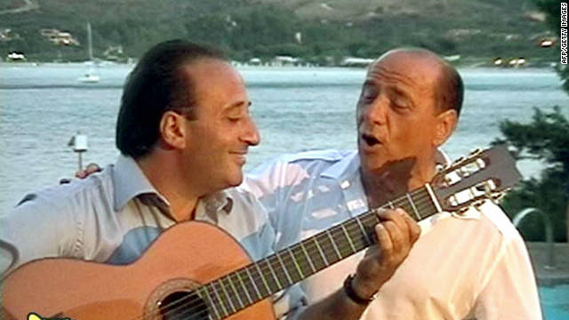 Flamboyant former Italian Prime Minister Silvio Berlusconi sings with guitarist Mariano Apicella during a private party in 2003.