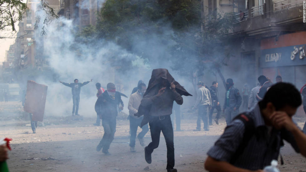 Protesters cover their faces as they flee tear gas fired by police on Sunday.