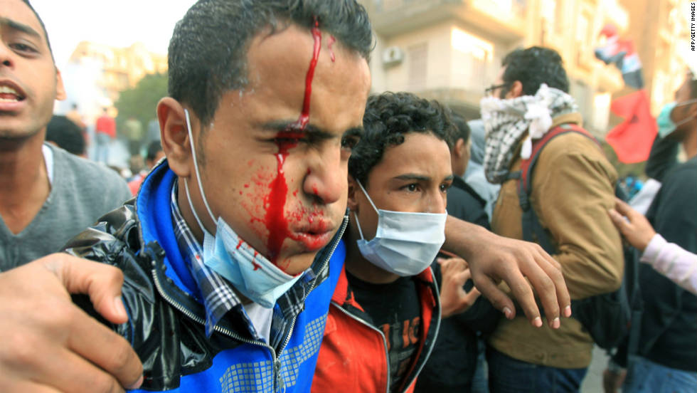 An injured Egyptian protester is helped away during clashes with security forces at Tahrir Square in Cairo on November 21, 2011.