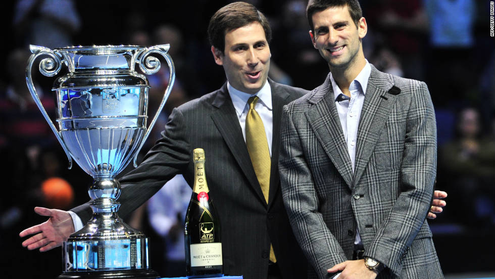 ATP World Tour executive chairman and president Adam Helfant, left, presents top-ranked Novak Djokovic with the player of the year trophy this week -- and a bottle of champagne provided by sponsor Moet & Chandon.