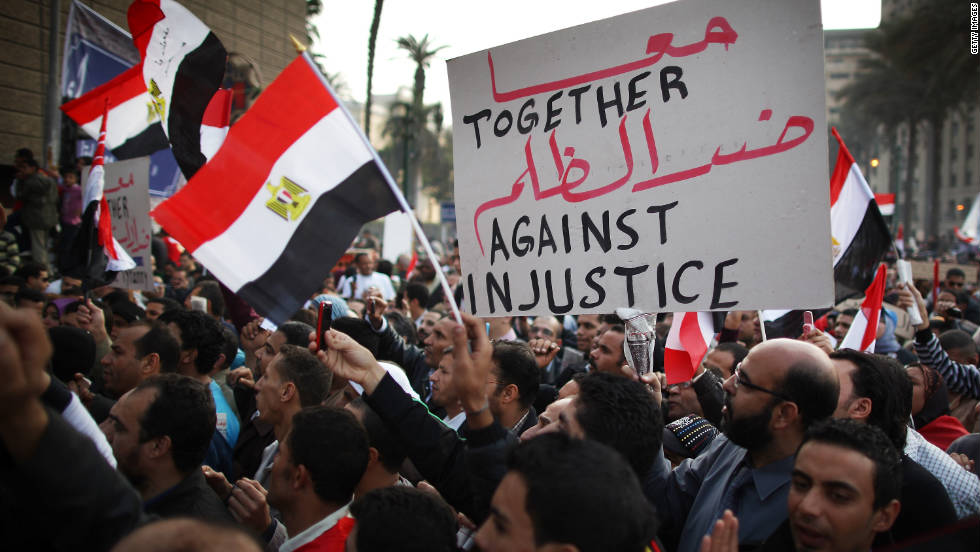Demonstrators wave flags and signs Friday in Tahrir Square.
