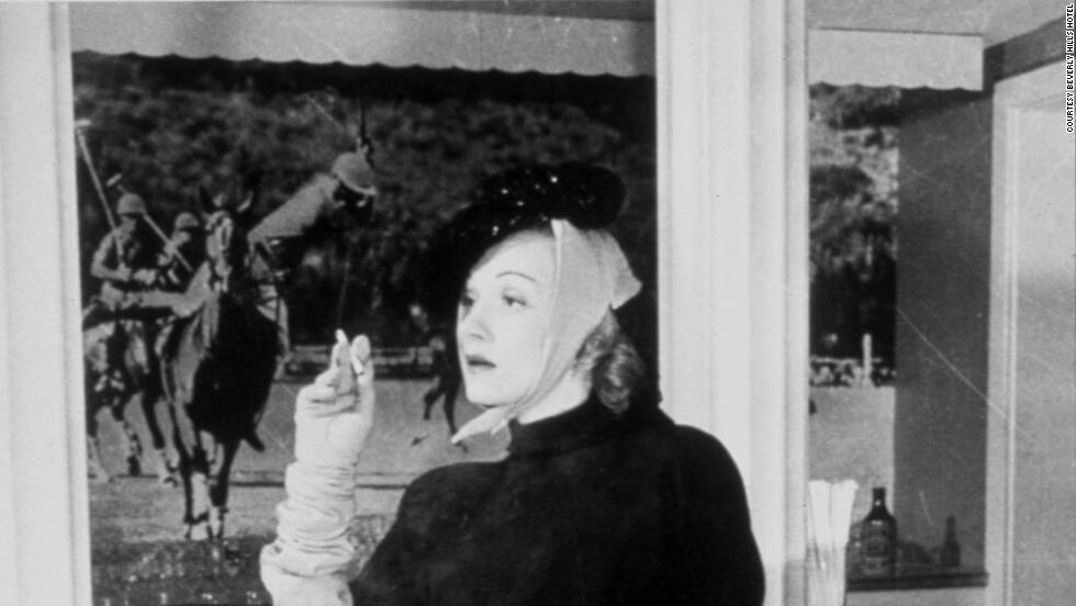 Marlene Dietrich convinced the Beverly Hills Hotel to ease its dress code so she could wear pants in the Polo Lounge. Behind her, the photo depicts a polo-playing Will Rodgers.