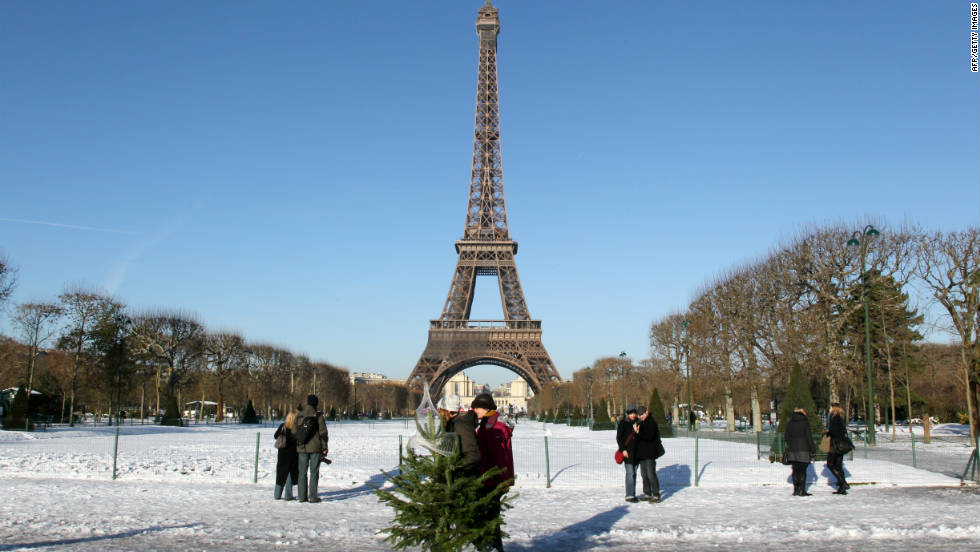 Christmas tree shoppers join tourists on a snow- covered Champ de Mars near the city's iconic Eiffel Tower.