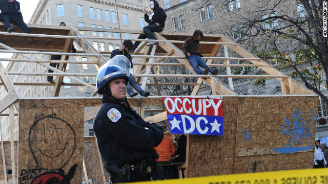Occupy DC protesters sit atop a wooden structure  at their encampment in Washington's McPherson Square on Sunday.