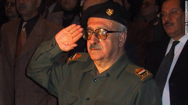 Tariq Aziz salutes as the Iraqi national anthem is played during a 2001 event.