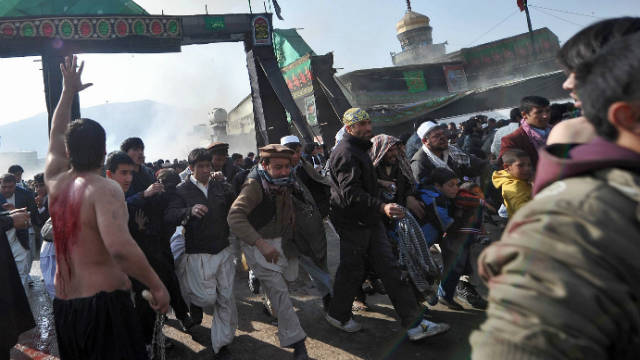 Afghans flee a bomb blast at a shrine in Kabul