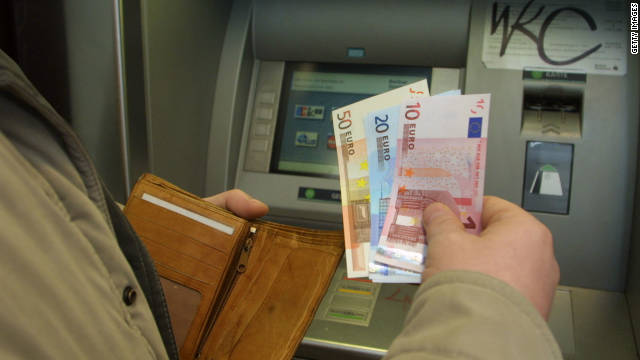 A man uses an ATM machine to get some new euro bank notes from his account January 1, 2002 in Berlin, Germany.