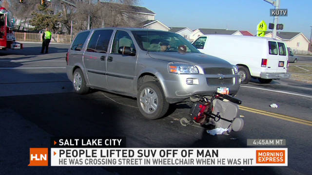 People lift SUV off man in wheelchair