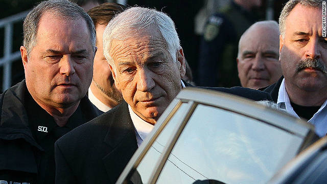 Former Penn State assistant football coach Jerry Sandusky is ecorted to his car while leaving the Centre County Courthouse, on December 13, in Bellefonte, Pennsylvania.
