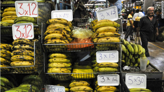 A man walks next to a banana stand in a public market in Caracas on May 06, 2011. Buying food has become a daily ordeal for many Venezuelans.