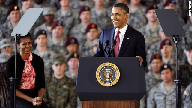 ROCK HILL, SC - DECEMBER 14: U.S. President Barack Obama speaks as first lady Michelle Obama listens during a tribute to the troops on December 14, 2011 at Fort Bragg, North Carolina. The U.S. is ending its war in Iraq and all U.S. troops are scheduled to be out of Iraq by December 31. (Photo by Davis Turner/Getty Images)