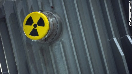 A picture taken on November 22, 2011 shows a radioactivity warning symbol on a 'CASTOR' (Cask for Storage and Transportation of Radioactive Material) container carrying highly radioactive nuclear waste which is part of a convoy waiting at the Areva's train station in Valognes, northwestern France, a day before leaving for Gorleben in Germany. Despite massive police forces deployment, anti-nuclear protests are expected in France and Germany against the transport of the eleven so-called 'CASTORS' containing nuclear waste. AFP PHOTO / KENZO TRIBOUILLARD (Photo credit should read KENZO TRIBOUILLARD/AFP/Getty Images)
