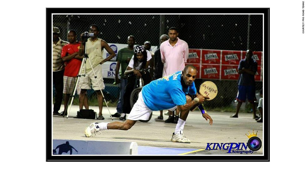 World champion White bends low to play a backhand return in match action.