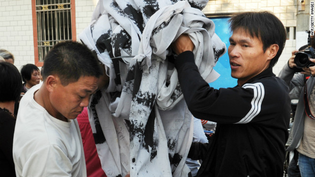 Villagers remove protest banners from the main street in Wukan, Guangdong Province on December 21, 2011