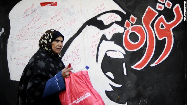An Egyptian woman walks past graffiti reading 'Revolution' off Tahrir Square in Cairo on December 21, 2011.