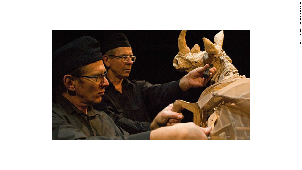 """Adrian Kohler (foreground) and Basil Jones (back) manipulate a rhino for the Handspring Puppet Company's """"Woyzeck on the Highveld"""" show."""