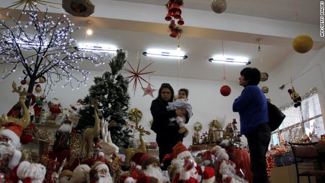 Palestinians look at the Santa Claus decorations in a Christmas shop in  Bethlehem on December 17, 2011.