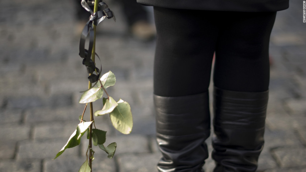 A woman in line holds a rose as she waits to pay respects to Havel on Thursday, December 22.