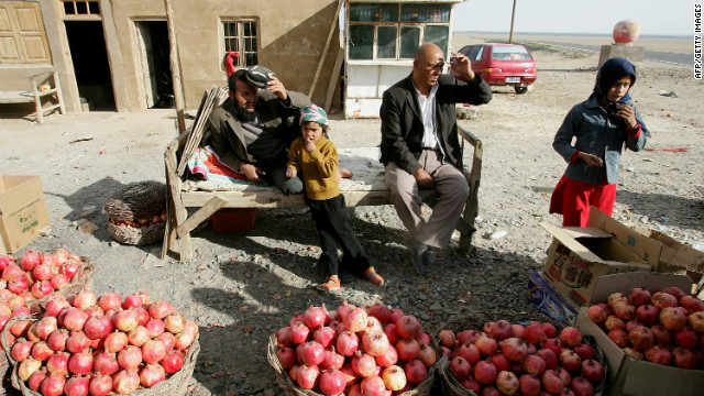 Chinese Uighurs sell pomegranates in Pishan, Xinjiang, in a file photo from 2006.