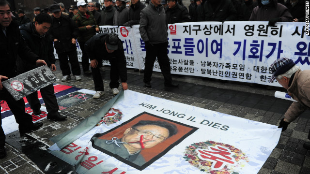 Anti-North Korea protesters place fmr leader Kim Jong-Il's portrait on ground during a demonstration in Seoul on December 28, 2011.