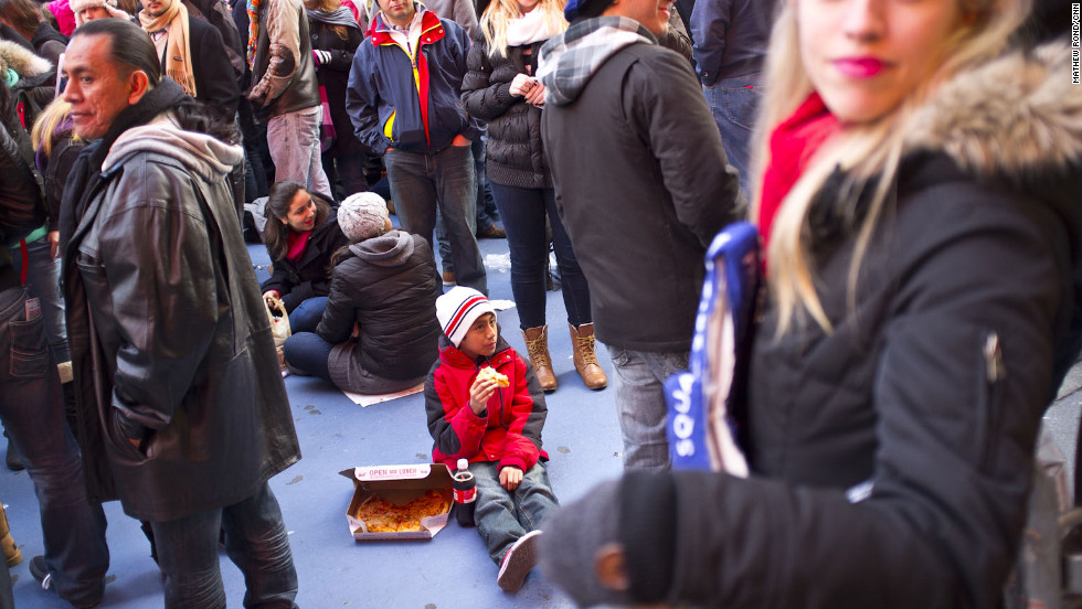 A young celebrator enjoys a slice of pizza in Times Square before the festivities begin.