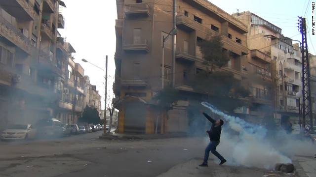 A protester in the flahspoint central Syrian city of Homs throws a tear gas bomb back towards security forces, on December 27, 2011.