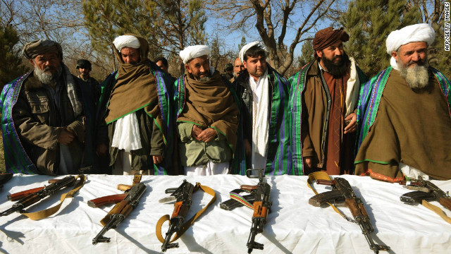 Taliban fighters stand near their weapons after joining Afghan government forces at a ceremony in Herat on December 29, 2011.