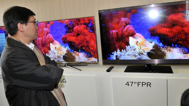 A journalist compares the 3-D televisions of Samsung (L) and LG (R) after a news briefing in Seoul.