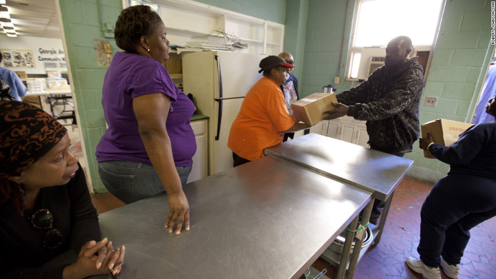 """Andono joins fellow Georgia Avenue Food Cooperative members in unloading groceries from a truck in Atlanta. """"If it were not for the co-op,"""" she says, """"a lot of us would not be able to survive. This is the bridge that helps get us over."""" The Bryants used to make $40,000, lived in their own home, and gave to others. She comes to the co-op to get groceries every two weeks. """"We went from the giving to the receiving,"""" she says."""