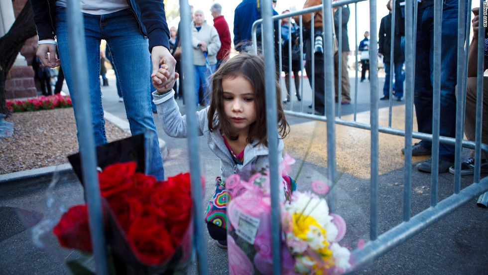 Rebecca Kraft, 4, places flowers at a memorial site in the Safeway parking lot on Sunday.