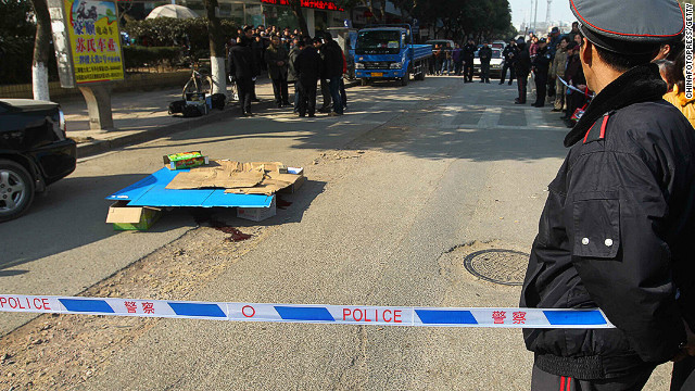 Police officers investigate the scene of the crime after a suspect allegedly killed a man during a robbery in Nanjing.
