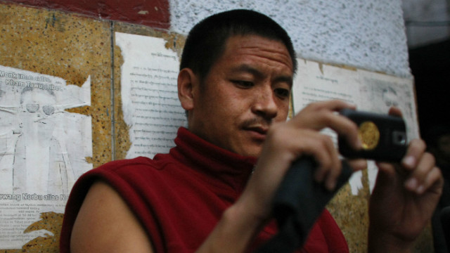 A monk in New Delhi in this file picture stands next to an image of a Tibetan monk that self-immolated in Tibet.