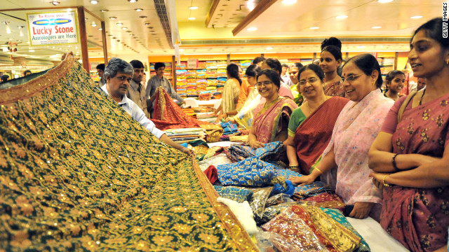 Indian women look at a display of sarees during the launch of a wedding collection at a mall in Hyderabad.