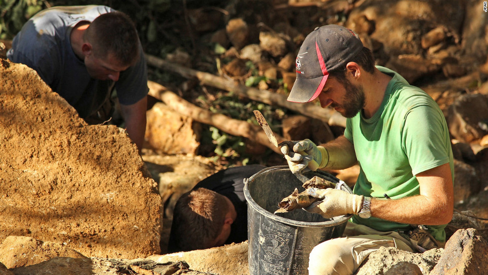 Sean Tallman, a Navy civilian and anthropologist from JPAC, examines items found beneath a boulder at a recovery site in Quang Nam Province, Vietnam.