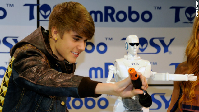 Justin Bieber holds a microphone in front of the mRobo Ultra Bass as he unveils the portable speaker and dancing robot.