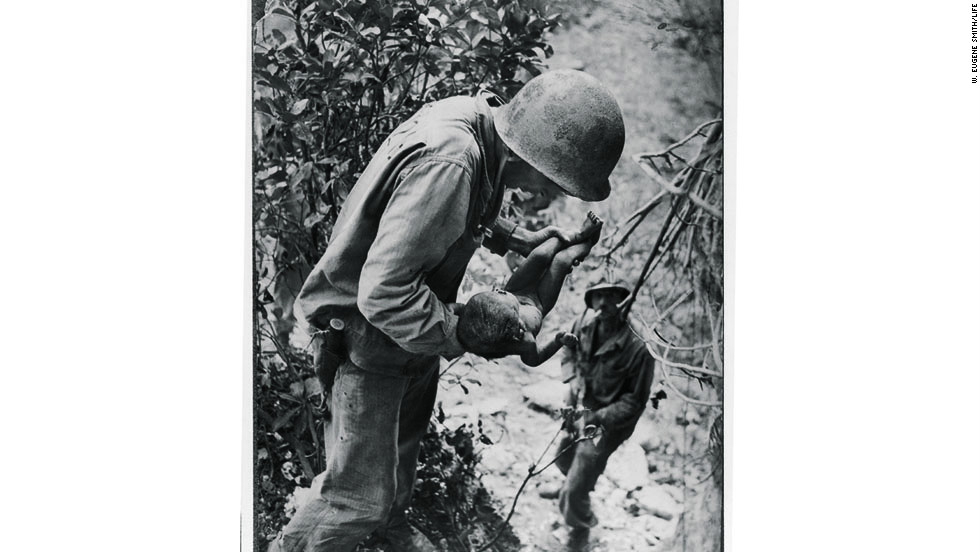 An American soldier comforts a wounded infant in Saipan.