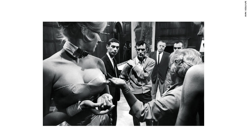 Hugh Hefner evaluates Bunny outfit alterations at the Chicago Playboy Mansion in 1965.